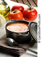 Tomato soup in a black casserole and ingredients