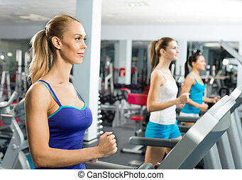 young women running on a treadmill, exercise at the fitness...