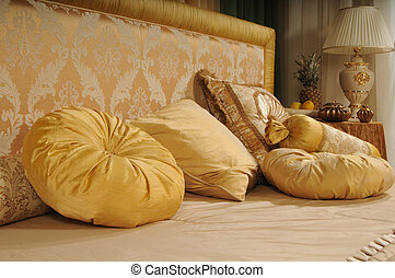 Decorative pillows on a bed at a headboard