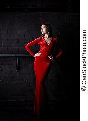 Beautiful woman posing in red long dress
