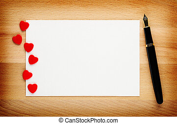 Blank Valentines card with red hearts and fountain pen on...