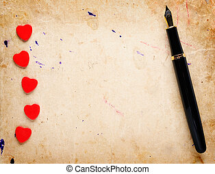 Red hearts and fountain pen on old paper background