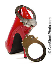 Handcuffs and high heel close up, on white background