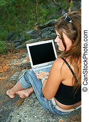 Girl with laptop - Female hiker taking a break at the edge...