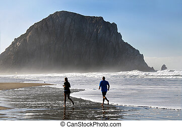 Joggers At Sunrise in front of the Morro Rock, Morro Bay...
