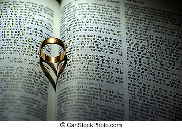ring and Bible - ring and heart shaped shadow over a Bible