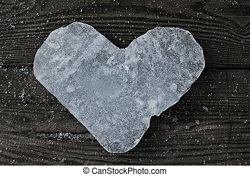 ice heart - heart from ice on the piece of wood