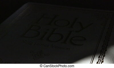 Bible - Holy Bible as time lapsed sun passes over.