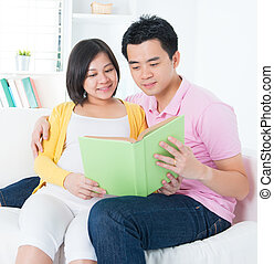 Asian couple reading book together, sitting on sofa
