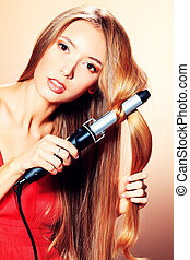 safe curling - Beautiful young woman doing hairstyle with...