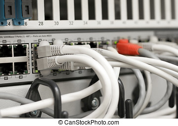 network hub and cables connected to servers in a datacenter