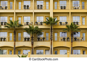 Hotel - Yellow hotel with balconies.