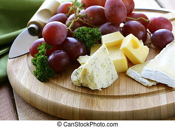 cheeseboard with cheese and grapes - cheeseboard with three...