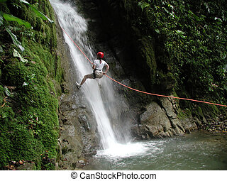 Woman Rappelling Falls - A woman scaling a challenging and...