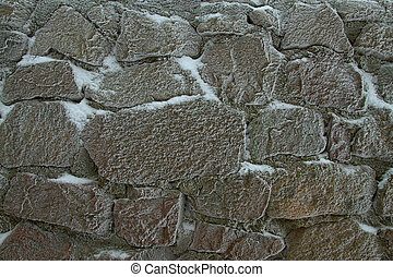 texture wall - stone wall covered with snow in sub-zero...