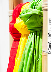 Red, green and yellow scarves. - Three scarves hanging from...