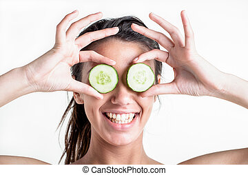 Happiness - A teenage female with two pieces of cucumber in...