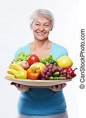 Healthy eating - Elderly woman with fruits and vegetables on...