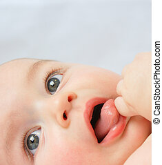 Baby boy\\\'s face - Close up shot of a baby boy sucking his...