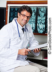 Doctor Sitting At Desk With Clipboard - Portrait of happy...