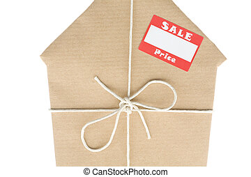 House Wrapped In Brown Paper With Sale Sticker - Studio Shot...