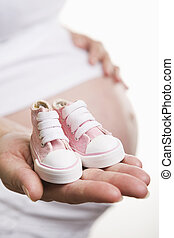 Pregnant woman holding baby shoes - Pregnant woman holding...