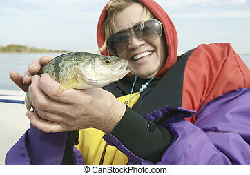 The Catch - Woman holding a perch that she caught out in...