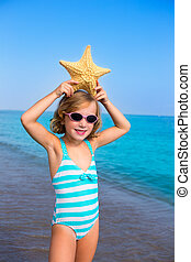 child kid girl in summer beach vacations with starfish and...