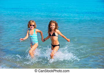 children girls friends running together in the beach shore...