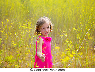 child kid girl in spring yellow flowers field and pink dress...