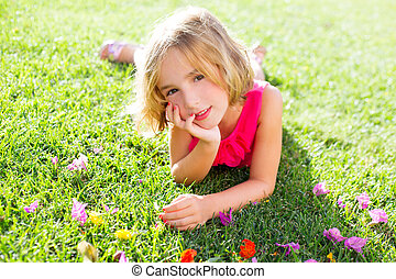 blond kid girl lying relaxed in garden grass with flowers
