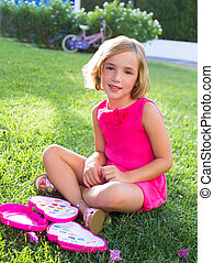 child kid girl playing with makeup set sitting in grass