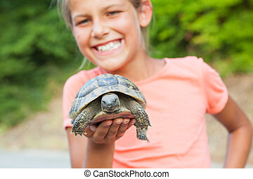 young girl and turtle - Young cute girl holding turtle....