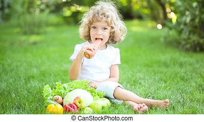Happy child eating vegetables