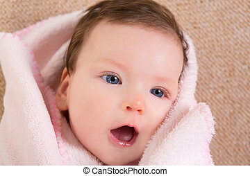 Baby little girl face portrait open mouth on pink blanket
