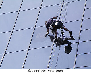 man cleaning windows on a high rise building