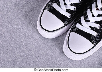 black canvas sneakers on grey textile background - A pair of...