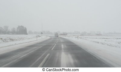 car blizzard road snow - cars going on winter rural road and...