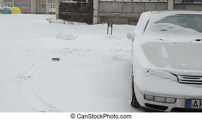 snow fall car parking - blizzard snow fall on white car...