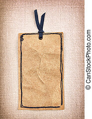 A vintage tag - A vintage paper tag on fabric background