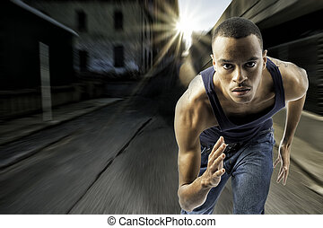 Young black male running in an urban setting - horizontal...