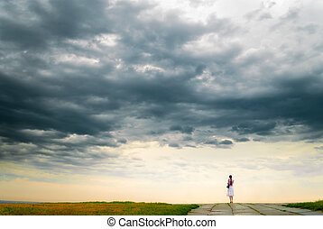 Girl looking at cloudy sky from bluff