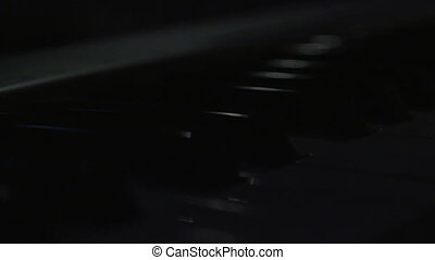 piano keyboard - Spot light passes over piano keyboard.