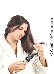 Beautiful woman with a hairbrush watching her hair