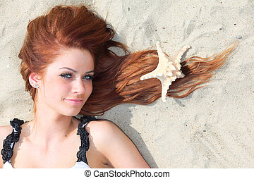 The beautiful girl lies on sea coast with shells nature...