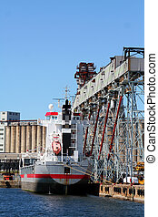 Container Ship - A container ship loading grain before...