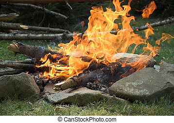 Camping - Campfire in the morning. Huge flames. Stones in...