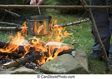 Cooking - Young man is preparing soup in pot on fire.