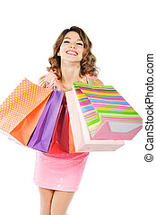 Young cheerful girl with shopping bags isolated on white -...