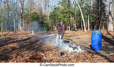 A man working a burning pile of trash and debris along side the edge of the woods